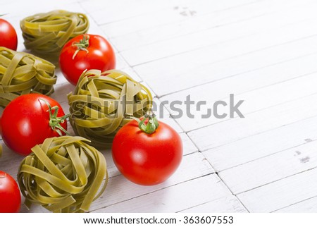 tomatoes with spinach tagliatelle pasta on white wood table