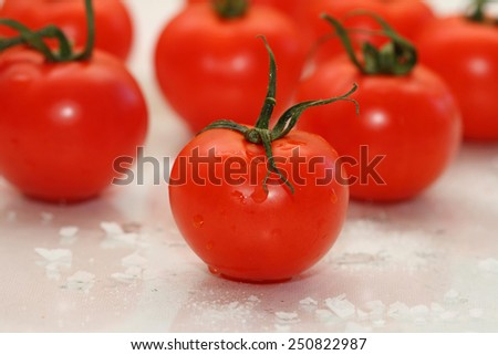 tomatoes with tails on the reflecting surface with coarse sea salt