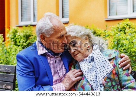 Toned image.. Elderly man tenderly embracing his elderly wife on a bench near a residential building in a modern city.