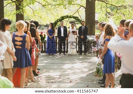 Toned photo of guests clapping to just married couple at outdoor wedding ceremony