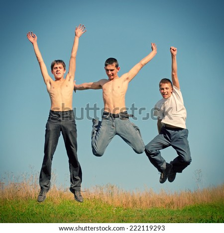 Toned photo of Three Happy Tennage Boys jumping
