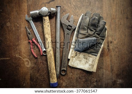 tools and leather gloves on wooden work table (vintage color effect)