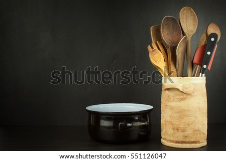 Tools cook on a wooden shelf. Kitchen utensils in a ceramic container on black background.