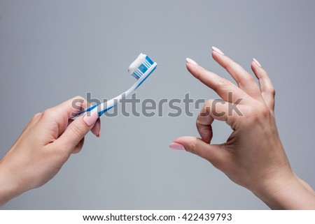 Toothbrush in woman's hands on gray