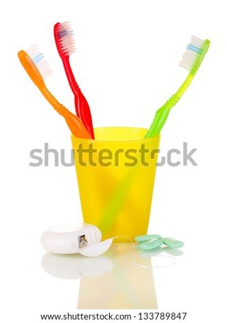Toothbrushes, chewing gum and dental floss isolated on white
