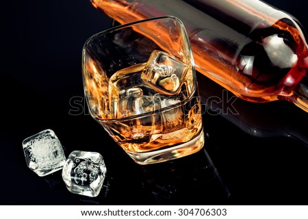top of view of glass of whiskey near bottle and ice cubes on black table with reflection, time of relax with whisky