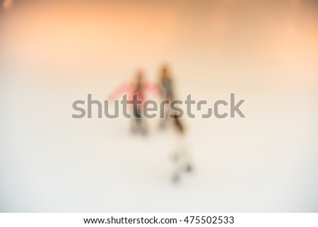 Top view blurred motion background of parents and kids play indoor ice skating in modern shopping mall. Defocused of indoor ice skating with people on the ice rink. Natural light from glass roof.