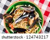 Top view of a green bowl full with spaghetti and mussels. This is a traditional Italian dish and it's very light and healthy. - stock photo
