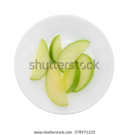 Top view of a group of green apple slices on a plate isolated on a white background.