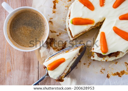 Top view of a homemade carrot cake with mascarpone cream cheese icing and handmade mini marzipan carrot decorations with a cup of hot black coffee