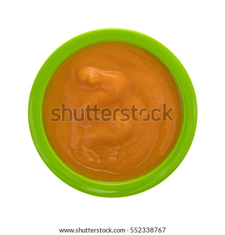 Top view of a serving of banana carrot and mango baby food in a green bowl isolated on a white background.