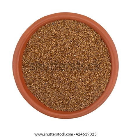 Top view of a small bowl of teff grain isolated on a white background.