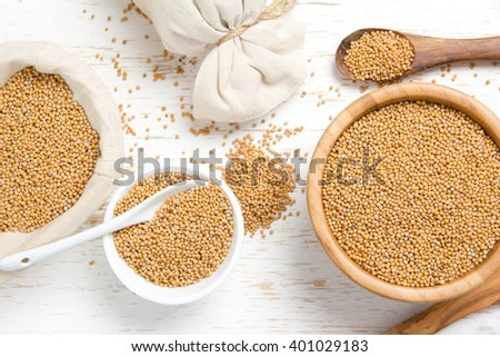 Top view of bowls full of mustard seeds on white wooden surface