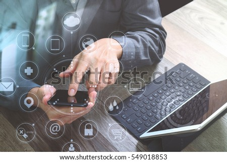 top view of businessman hand using smart phone,mobile payments online shopping,omni channel,digital tablet docking keyboard computer in modern office on wooden desk,virtual interface icons screen