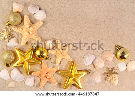 Top view of Christmas decorations and seashells and starfish on a beach sand
