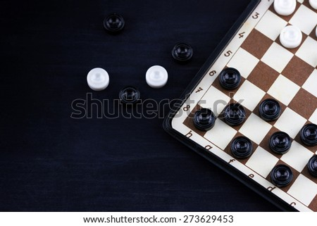 Top view of small travelling board for playing checkers on dark wooden background