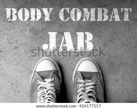 Top View of Sneaker Shoes on the floor with the text: Body combat jab