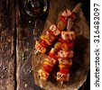Top View of Three Cooked Fish Kebabs on a Rustic Wooden Table with Oil - stock photo