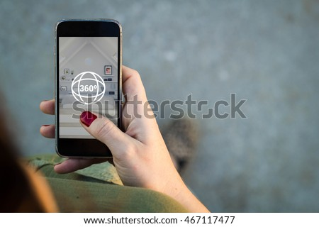 Top view of woman walking in the street surfing 360 degree view in her mobile. All screen graphics are made up.