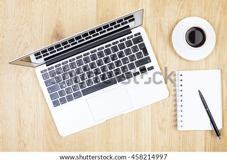 Top view of wooden desktop with laptop, spiral notepad, pen and coffee cup