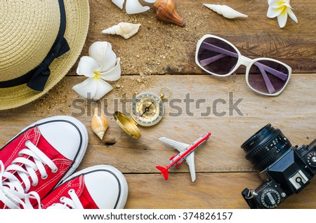 Top view travel accessories for summer on wooden background