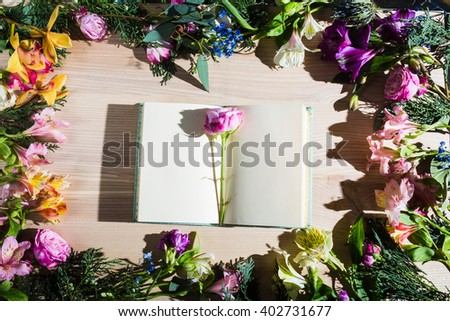 Top view workspace with blank notebook and fresh pink flowers on wooden table background .