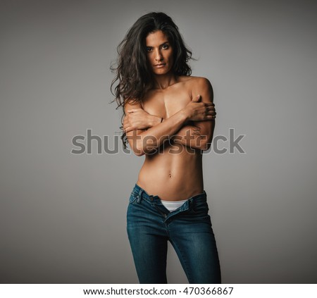 Topless woman standing in grey room stares ahead at camera while wearing unzipped jeans and having long brown hair