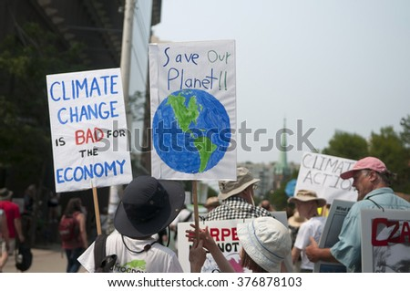 TORONTO - JULY 5 : Protesters with signs urging to save the planet with climate control  during the Jobs,Justice and Climate rally on July  5, 2015 in Toronto, Canada.