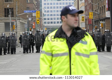 TORONTO-JUNE 26:  A police officer standing on the first line of control while other riot police officers stand on the second line during the G20 Protest on June 26, 2010 in Toronto, Canada.