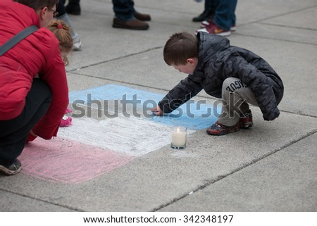 Toronto November 14, 2015 Crowds at Nathan Phillips Square for a silent vigil for those lost in the attacks on Paris. Children colour a French flag on the ground in chalk in solidarity with France.