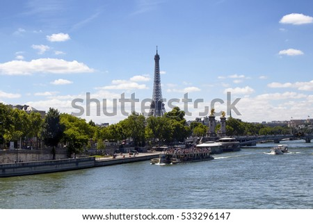 Tour boats are on Seine River in Paris. Trees, Pont Alexandre III bridge and Eiffel tower are in the view.