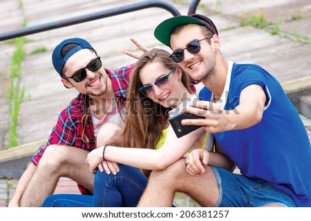 Tourism threesome. Young friends have fun together on the street and smile at each other. Funny guys make Selfie