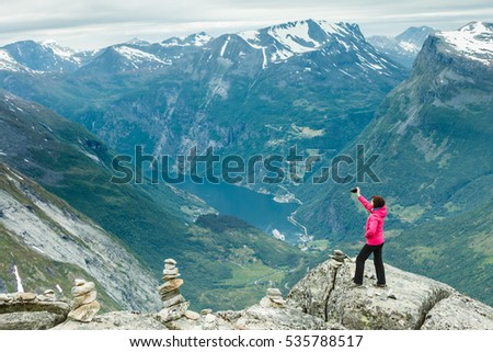Tourism vacation and travel. Female tourist taking photo with camera, enjoying Geiranger fjord and mountains landscape from Dalsnibba Plateau viewpoint, Norway Scandinavia.