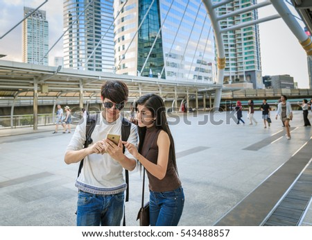 Tourist Asian Couple Sightseeing In City Trip Pointing Map In Smart phone For Direction