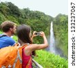 Tourist couple on Hawaii taking pictures of the famous Akaka Falls waterfall on Hawaii, Big Island, USA. Happy cheerful young multicultural couple tourists on travel. - stock photo