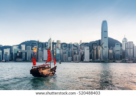 Tourist sailboat crosses Victoria harbor from Kowloon side to the Hong Kong Island. Scenic view of traditional Chinese wooden sailing ship with red sails and skyscrapers of downtown at evening.