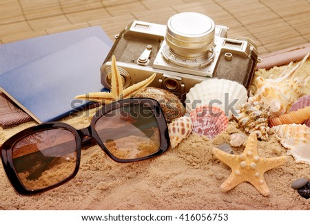 Tourist stuff. Vintage photo with sunglasses, seashells, passport documents and retro camera. Summer holiday concept