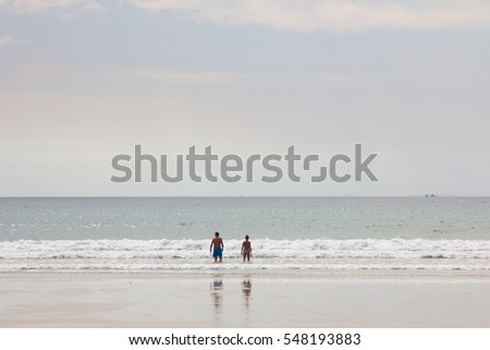 Tourist walking along the shallow ocean during the low tide