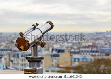 Touristic telescope overlooking Montmartre hill with scenic city view in Paris, France