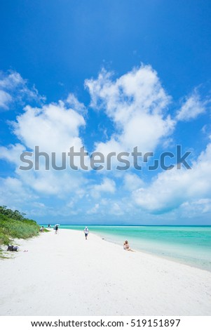Tourists on white sand tropical beach, Taketomi Island of the Yaeyama Islands, Okinawa, Japan
