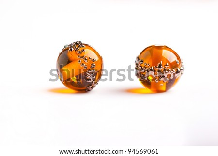 Tow orange glass beads closeup on white background