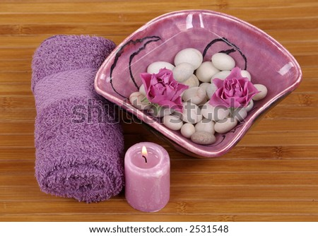 Towel, pink roses, pebbles and candle