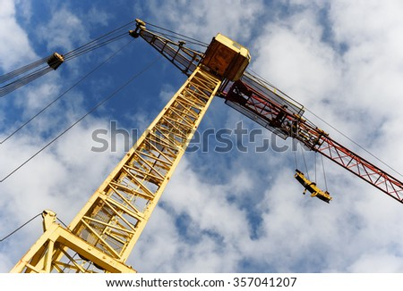 Tower crane on a background of blue sky and white clouds. Bottom.