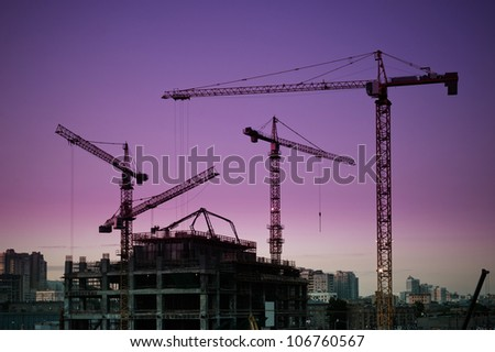 tower cranes around construction site at dusk