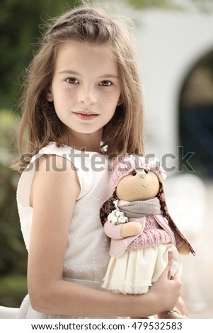 Toy handmade. Beautiful girl with freckles. A child with a soft toy.