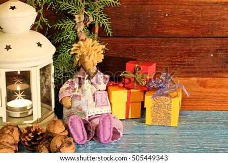 Toy small sleepyhead with three gift boxes on wooden boards. Christmas concept. Still life