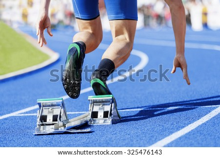 Track and field runner starts out of the blocks.