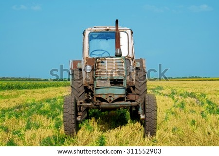 Tractor in field on blue sky background