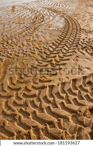 Tractor tire tracks on beach sand