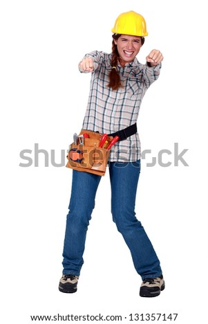 Tradeswoman gripping an invisible object and squinting